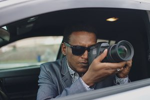 Paparazzi man sitting inside car and photographing with dslr camera