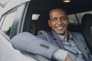 Portrait of serious businessman sitting inside car and smiling into camera outdoors