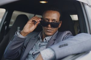 Portrait of serious businessman sitting inside car put of sunglasses and smiling into camera outdoors
