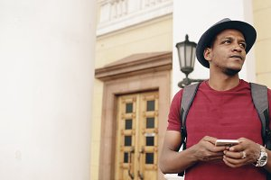 African american smiling tourist man using smartphone online map to find right directions standing at street