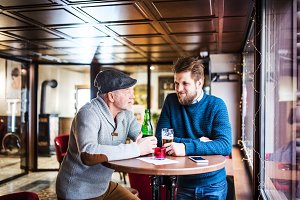 Senior father and his young son in a pub.