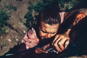 A young man climbs up a cliff, close