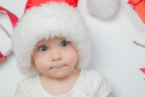 Baby lying with presents in santa hat on white background
