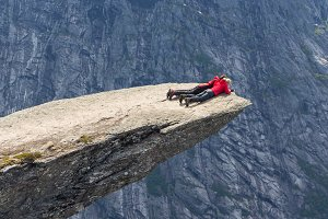 People lie on Trolltunga rock