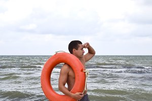The man on the beach with a lifebuoy