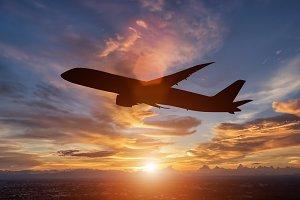 passenger plane flying in sunset.