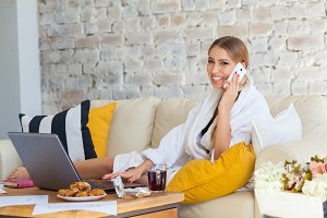 Female freelancer in a white coat clothing working remotly from her dining table in the morning. Houses on a sofa on a white brick wall background. Architect, blueprints. talking on the phone.