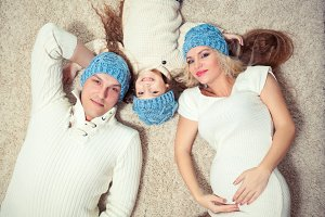 Top view of cute little girl and her beautiful young parents looking at camera and smiling while lying on the floor at home. in a winter sweater and hat, the concept of Christmas. pregnancy.