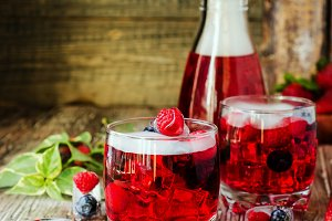 Summer berry lemonade with frozen berries on a wooden rustic table, selective focus