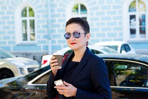Beautiful brunette woman with short hair and glasses standing in the street, drinks a coffee. The concept of business time