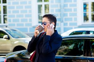 Beautiful brunette woman with short hair and glasses standing in the street, drinks a coffee and talk the phone. The concept of business time.