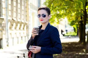 Beautiful brunette woman with short hair and glasses standing in the street, drinks a coffee and talk the phone. The concept of business time