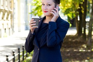 Beautiful brunette woman business woman talking on the phone and holding a coffee in hand.