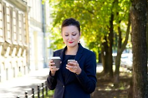Beautiful brunette woman with short hair keeps the phone in hand,gaining number keys, texting a message and smiling. The concept of business time.