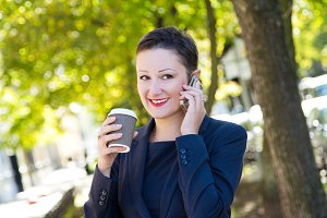 Beautiful brunette business woman talking on the phone and drinks a coffee