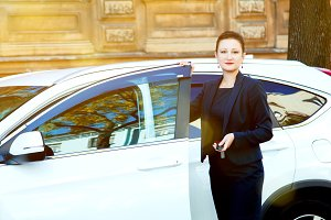 beautiful woman in a business suit opens the door with the keys in the hands of your car. The girl checks the alarm great car.