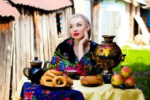 Russian girl sitting at a wooden table in the countryside in a traditional headscarf and drinks tea from a samovar.Russian traditions