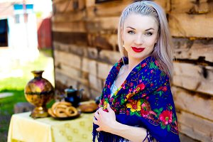 Russian girl in a national scarf in the village. Russian traditions