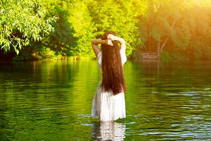 Girl with very long and thick dark hair standing in the water in the lake in the woods.