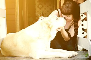 The concept of human and animal friendly. A girl and a big white dog gazing into each other's eyes, embrace and kiss.