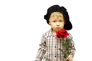 Cute baby with a rose in his hands. The concept of childhood, holiday, charity and love. Banner advertising. Copyspace.