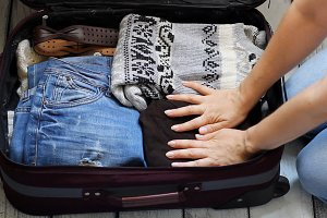 Holiday and travel. Trip and adventure.Packing warm clothes in a suitcase. Baggage.