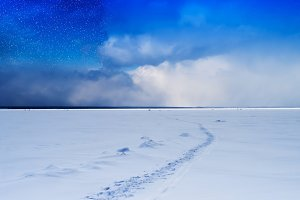 Stars on frozen lake with footprints path