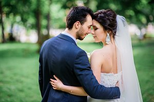 Groom hugs stunning brunette bride
