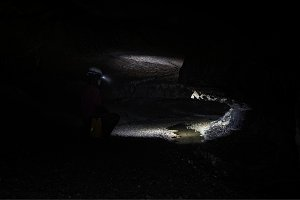 Woman with headlamp inside cave