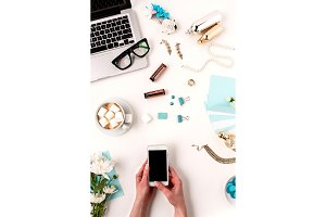 The female hands and smart phone against blue objects on white