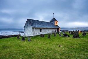 Small village church with cemetery in Kirkjubour, Faroe Islands