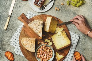 Cheese platter with female hands reaching to food, flat-lay