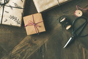 Flat-lay of gift boxes, rope, fur branches, scissors, square crop