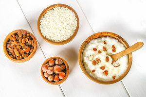 Rice milk porridge with nuts and raisins in wooden bowls on a white wooden table.