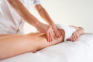 Detail of hands massaging human calf muscle.