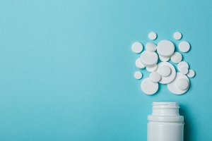 Medical concept - different shape white pills on blue background