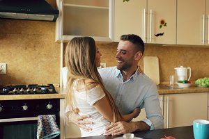 Attractive young couple embracing early morning in the kitchen while man have breakfast