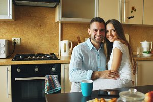 Portrait of happy smiling couple sittting in the kitchen early morning at home