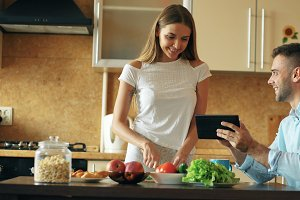 Attractive couple chatting in the kitchen early morning. Handsome man using tablet while his girlfriend cooking
