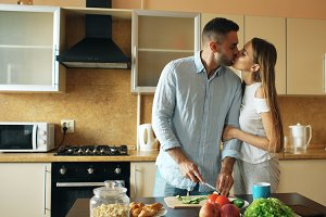 Happy young couple in the kitchen. Handsome man meet and kiss his girlfriend early morning