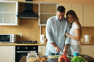 Happy young couple in the kitchen. Handsome man meet his girlfriend early morning