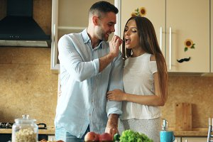 Happy young couple in the kitchen. Handsome man meet and feed his girlfriend early morning
