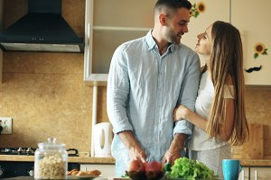 Portrait of loving couple smiling in the kitchen at home