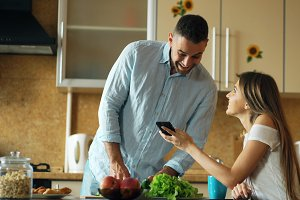 Attractive couple in the kitchen early morning. Beautiful girl sharing social media on smartphone with her boyfriend