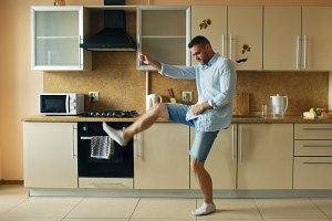Handsome young funny man dancing in kitchen at home in the morning and have fun on holidays