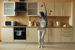 Cheerful young funny woman dancing and singing with ladle while having leisure time in the kitchen at home