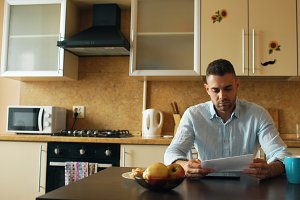 Upset young man reading letter with unpaid bill in the kitchen at home