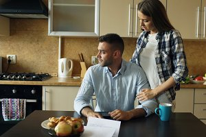 Upset young man reading unpaid bills and hugged by his wife supporting him in the kitchen at home