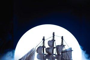 Sail ship in light of full moon. Wooden model on dark background. Conceptual marine still life.
