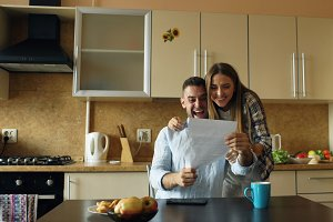 Attractive happy couple recieve good news unfolding letter in the kitchen while have breakfast at home